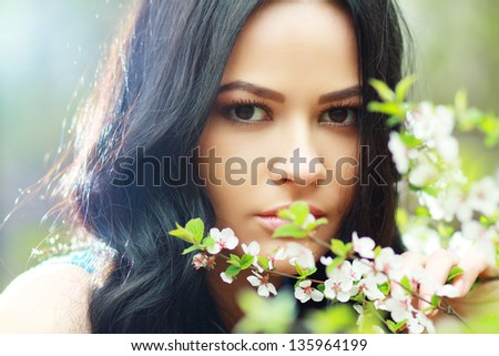 beautiful happy brunette woman in the park on a warm spring day with blossom flowers around her - stock photo