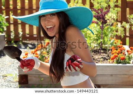 Beautiful happy brunette young woman working in the garden.  - stock photo