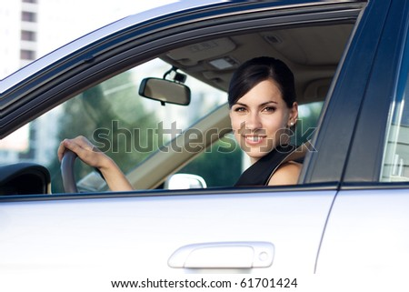 Beautiful happy businesswoman driving her car - stock photo