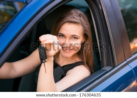 Beautiful happy businesswoman sitting in her car - stock photo