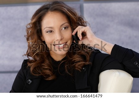 Beautiful happy businesswoman talking on mobile phone.