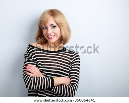 Beautiful happy casual blond woman with folded arms looking with smiling on blue background - stock photo