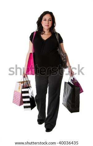 Beautiful happy Caucasian pregnant brunette woman holding shopping bags while walking, isolated - stock photo