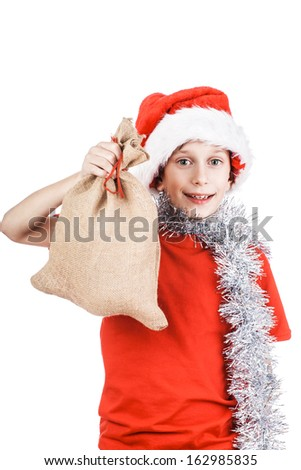 Beautiful happy child dressed as Santa holding a bag with Christmas presents smiling