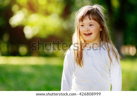 Beautiful happy child suffering from Down syndrome smiling outdoors - stock photo