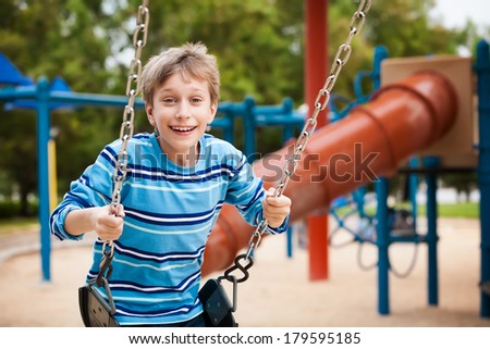 Beautiful happy child swinging on a playground in a sunny park and smiling. - stock photo