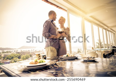 Beautiful happy couple having romantic dinner at sunset in a luxury restaurant - Woman and her husband celebrating wedding anniversary - stock photo