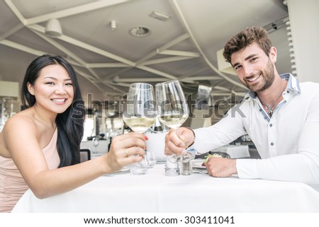 Beautiful happy couple having romantic dinner in a luxury restaurant - Woman and her husband celebrating wedding anniversary - Multiracial lovers toasting wine glasses - stock photo