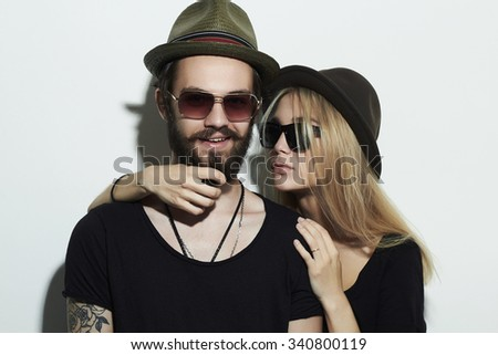 beautiful happy couple in hat wearing trendy glasses together. Hipster smiling boy and girl. Bearded young man and blonde model in sunglasses - stock photo