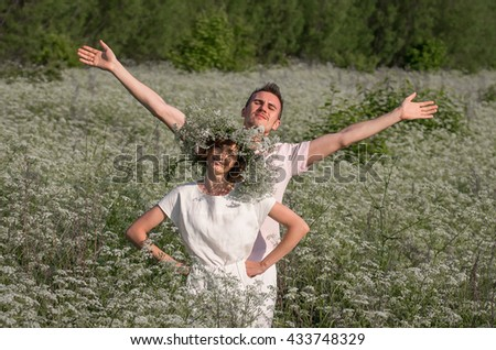 Beautiful happy couple on white floral field, having fun on floral glade, summer nature, love concept.