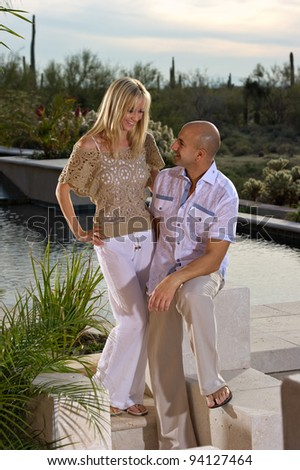 Beautiful happy couple posing next to a pool.   A green winter desert landscape is in the background. - stock photo