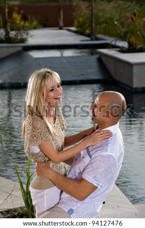 Beautiful happy couple posing next to a pool.   He is sitting and she is standing. - stock photo