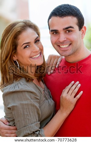 Beautiful happy couple smiling and hugging outdoors - stock photo