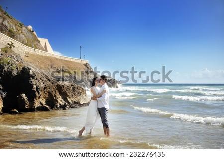 beautiful happy couple together embracing on the beach near sea, Sperlonga, Italy - stock photo