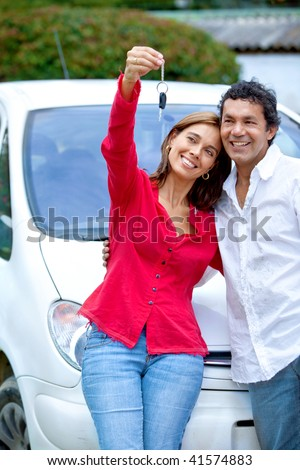 Beautiful happy couple with new car outside - stock photo