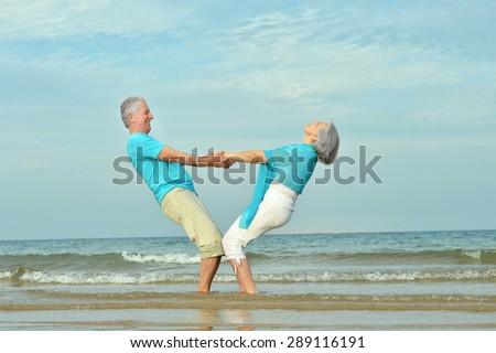 Beautiful happy elderly couple walking along the seashore - stock photo