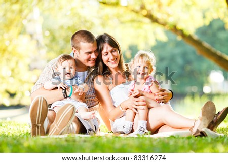 Beautiful happy family enjoying in the park - stock photo
