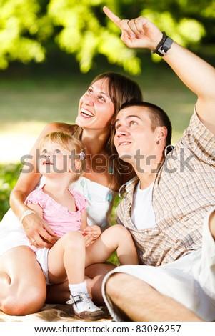 Beautiful happy family having fun in the park - stock photo