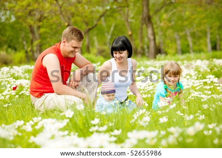 Beautiful happy family having fun on the meadow - stock photo