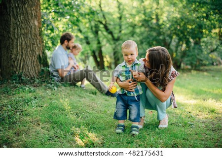 Beautiful happy family of four having fun in the park. Happy parenting. Father with daughter and mother with son.