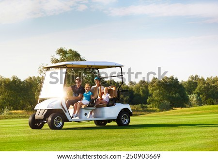 Beautiful happy family portrait in a cart at the golf course - stock photo