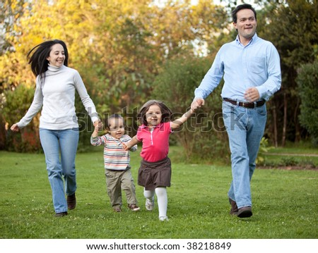Beautiful happy family running outdoors and smiling - stock photo