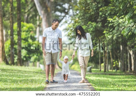 Beautiful Happy family together young parents in white clothes walking with their baby daughter in the park on a sunny summer day.