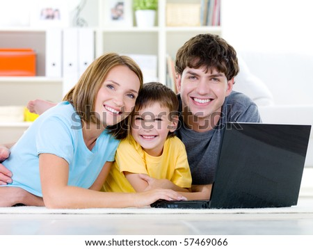 Beautiful happy family with little son relaxing at home with laptop - indoors - stock photo