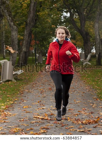 Beautiful happy female athlete jogging in park on a lovely autumn day. - stock photo