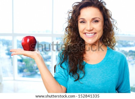 Beautiful happy female holding an apple with copy space - stock photo