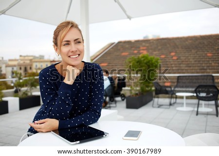 Beautiful happy female smiles for someone while sits with digital tablet in cafe during coffee break, young cheerful female student enjoys rest after work on portable touch pad while relaxes in bar