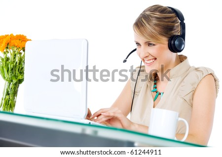 Beautiful happy female with headset sitting behind desk with laptop - stock photo