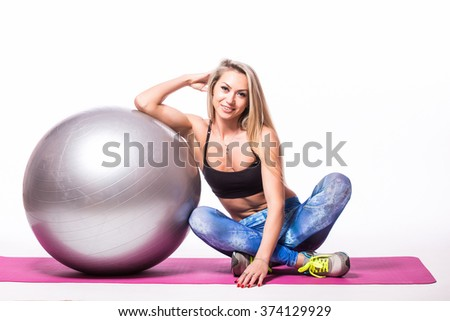 Beautiful happy fitness girl in tracksuit sitting and posing with grey fitball isolated over white background