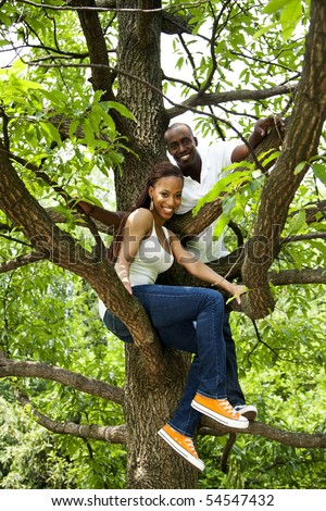 Beautiful happy fun smiling African American couple in tree, wearing white shirts and blue jeans. - stock photo