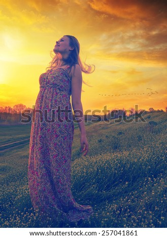 Beautiful happy girl enjoying sunny spring day on the meadow.   - stock photo