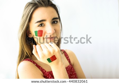 Beautiful happy girl, football fan, ronaldo supporter with portugal flag on face closeup - stock photo