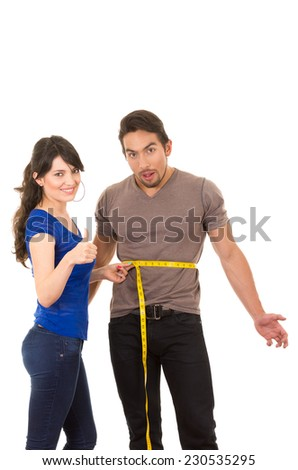 beautiful happy girl holding measuing tape around handsome muscular man's stomach concept of dieting fitness weightloss  isolated on white - stock photo