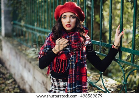 Beautiful happy girl in red hat and scarf walking in the autumn park