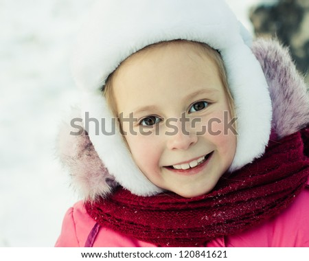 Beautiful happy girl in the red jacket winter outdoors.