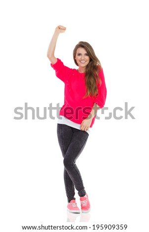 Beautiful happy girl is raising fist. Happy young woman celebrating success with arm raised. Full length studio shot isolated on white. - stock photo