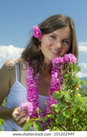 Beautiful, happy girl smelling a rose in a rose field wearing a garland of roses - stock photo