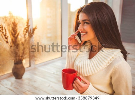 Beautiful happy girl talking on the phone with a cup in hand sitting on the floor near a window at home - stock photo