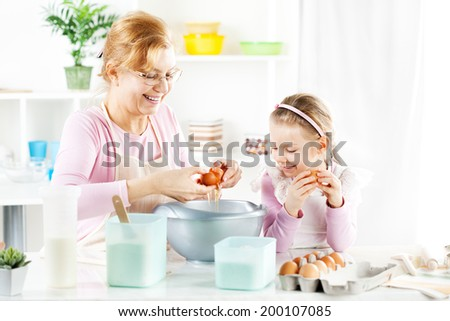 Beautiful happy grandmother and granddaughter making Dough in a kitchen.  - stock photo
