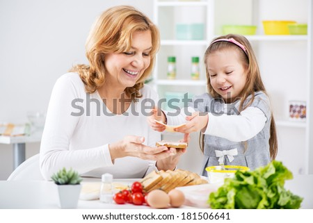 Beautiful happy grandmother and her cute granddaughter making a Sandwich in the kitchen. - stock photo