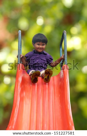 Beautiful & happy indian girl ( kid ) on park slider on a summer day. This girl's photo is on green background with clipping path showing summer time playground & a schoolgirl playing on a slider  - stock photo