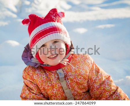 Beautiful happy kid in jacket in the winter outdoors.