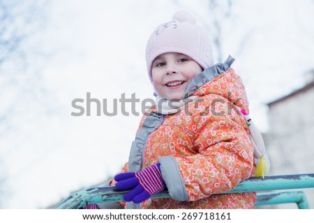 Beautiful happy kid in winter clothes. - stock photo