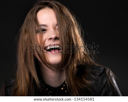 Beautiful happy laughing woman in rock style on black background