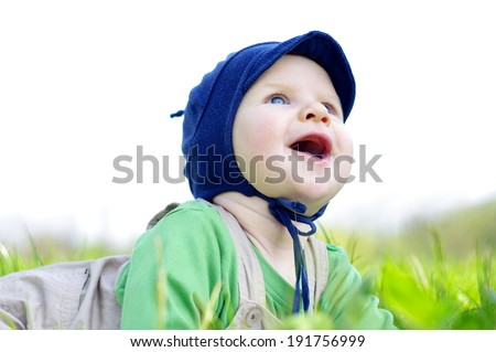 Beautiful happy little baby boy in hat looking on sky, lying on a green meadow on the nature in the park  - stock photo