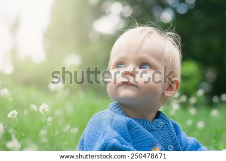 Beautiful happy little baby girl sitting on a green meadow on the nature in the park  - stock photo
